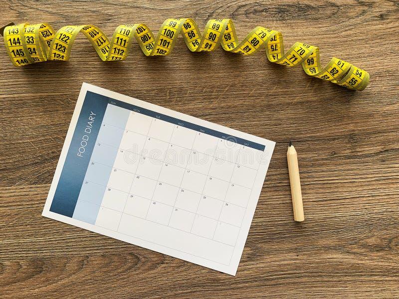 用餐计划概念 测量的磁带和用餐计划在木背景 图库摄影