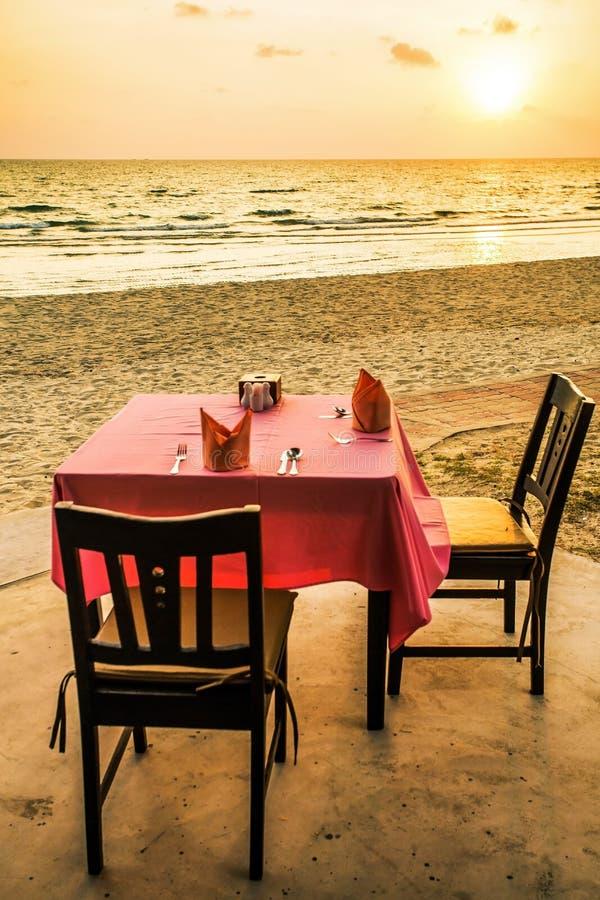 用餐tableon白色沙子靠岸有日落视图 图库摄影