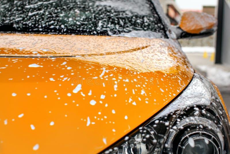 用香波泡沫报道的黄色汽车前面,当洗涤在carwa 免版税库存图片
