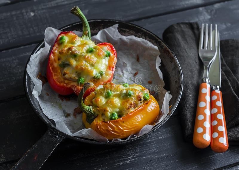 用鸡、绿豆和无盐干酪充塞的烤胡椒,在黑暗的木背景 免版税库存图片