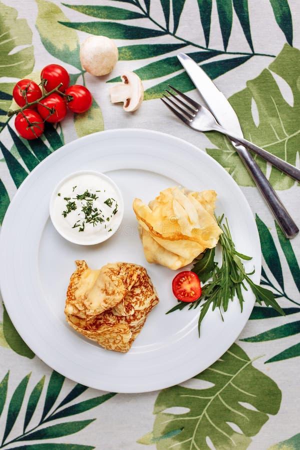用鸡和蘑菇充塞的滚动的可口绉纱在白色板材服务与酸性稀奶油 薄煎饼是舱内甲板 免版税库存照片