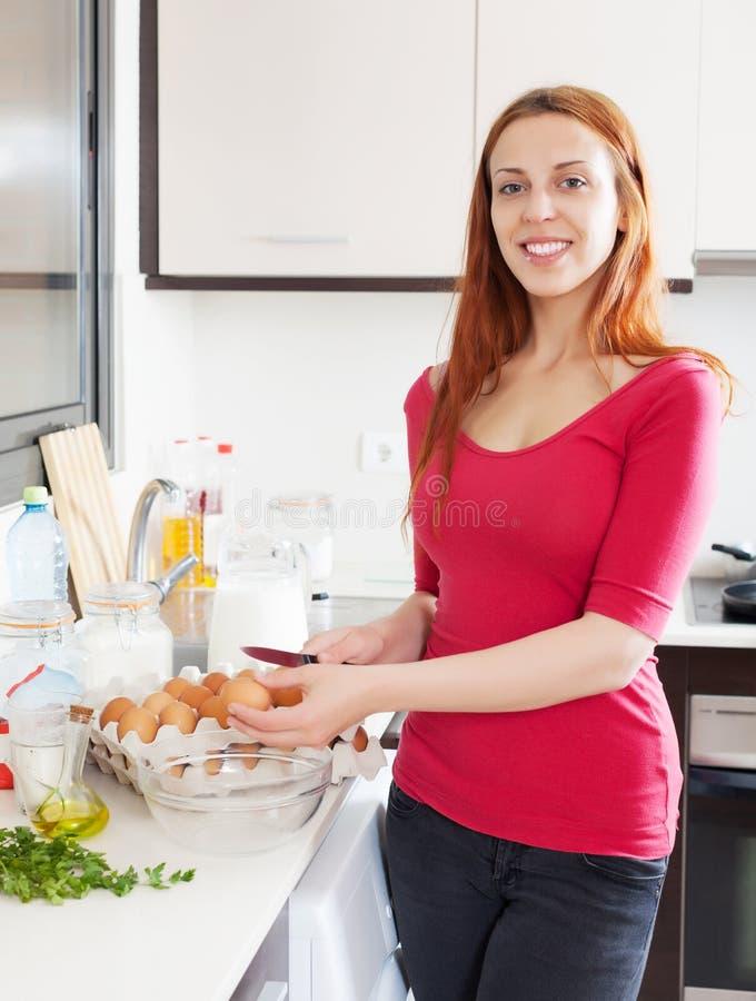 用鸡蛋烹调煎蛋卷的Cheeful主妇 免版税图库摄影