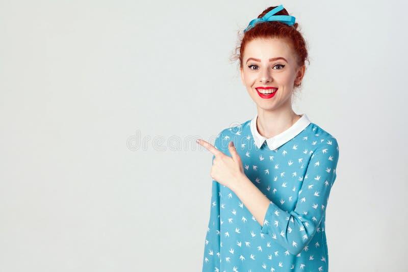 年轻用头发小圆面包指向她的食指的红头发人白种人女孩,表明在白色死墙上的拷贝空间您的cont的 免版税库存图片