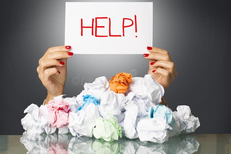 用wastepaper盖的被注重的雇员在工作,请求帮忙 免版税库存照片