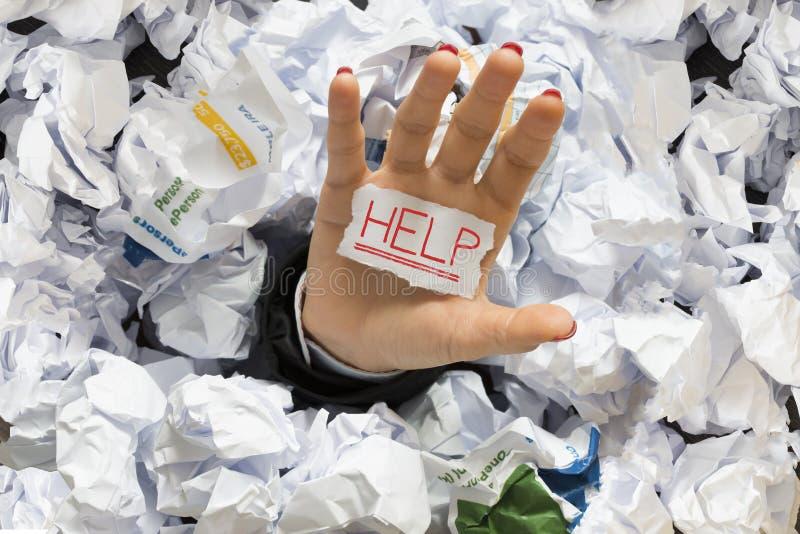 用wastepaper盖的被注重的雇员在工作,请求帮忙 库存照片