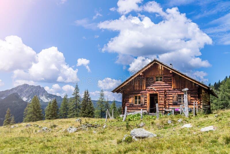 田园诗山风景在阿尔卑斯:山瑞士山中的牧人小屋、草甸和天空蔚蓝 图库摄影