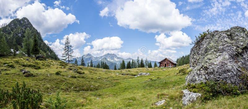 田园诗山风景在阿尔卑斯:山瑞士山中的牧人小屋、草甸和天空蔚蓝 库存照片