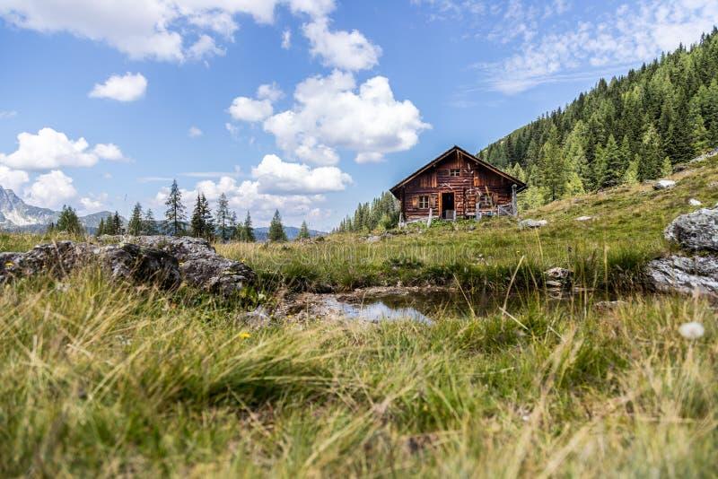 田园诗山风景在阿尔卑斯:山瑞士山中的牧人小屋、草甸和天空蔚蓝 免版税库存照片