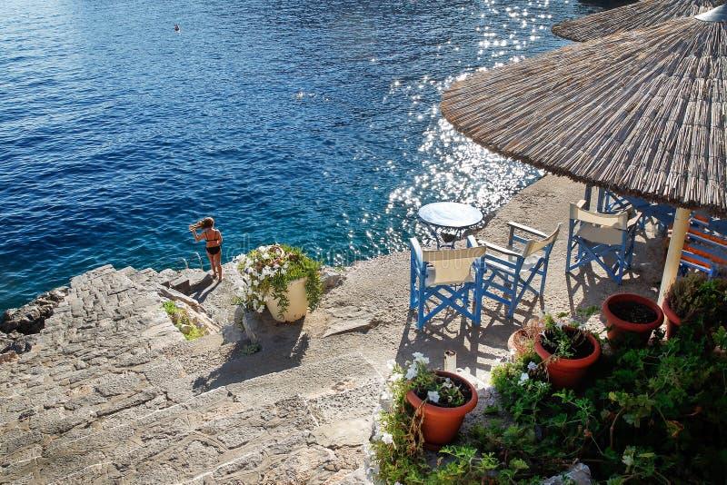 田园诗希腊海岛九头蛇 2把椅子和一张小桌 对水的急剧下降 库存照片