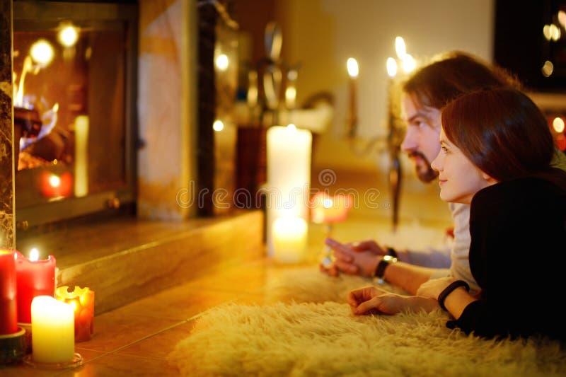由一个壁炉的愉快的夫妇在圣诞节 免版税图库摄影