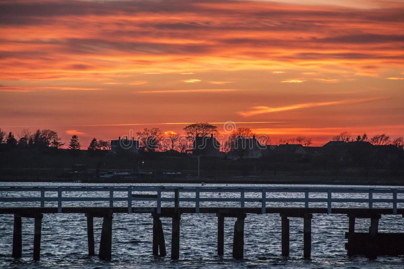 由一个码头的日落在纽波特罗德岛 库存图片