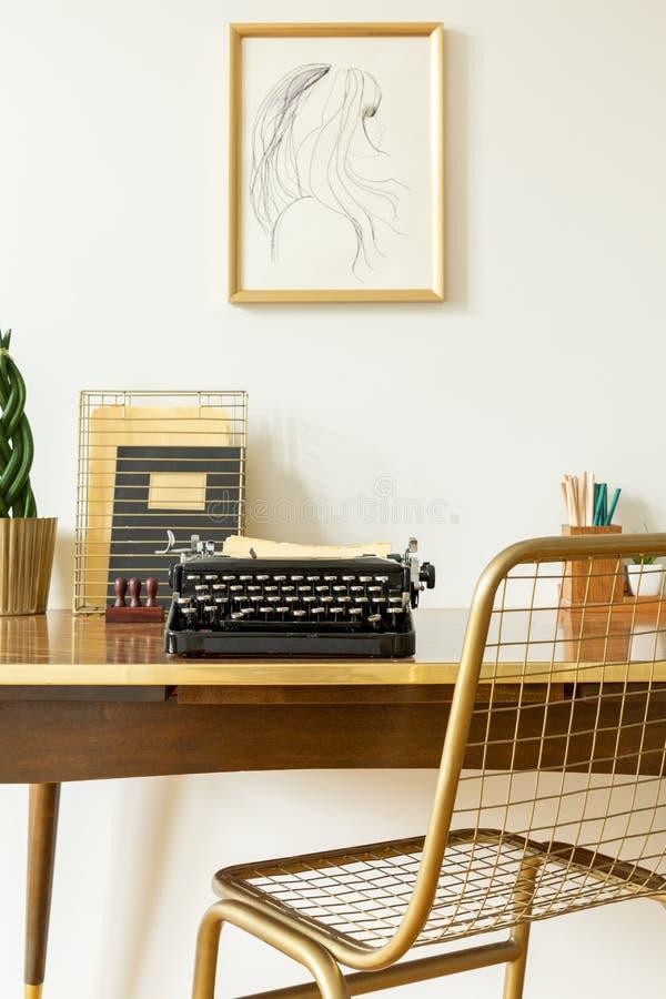 由一张木书桌有黑色的,在艺术性的家庭办公室内部的葡萄酒打字机的工业,金黄净椅子 免版税图库摄影