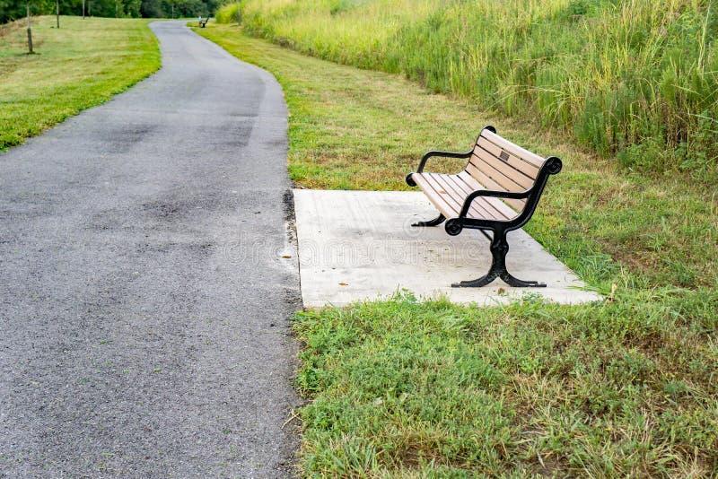 由一条人行道的公园长椅 免版税库存照片