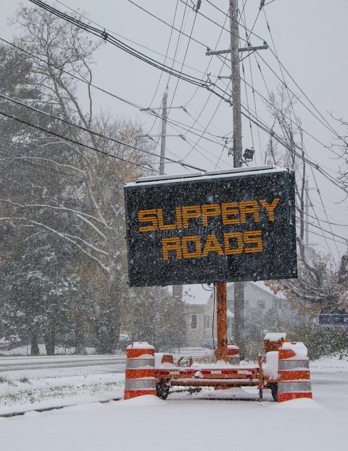 由一条积雪的路的边的电公路交通流动标志在与溜滑路的雪下跌的警告的冬天 免版税库存图片