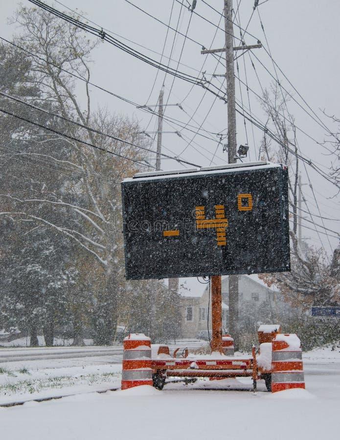 由一条积雪的路的边的电公路交通流动标志在与落的雪的冬天表明温度 免版税库存照片