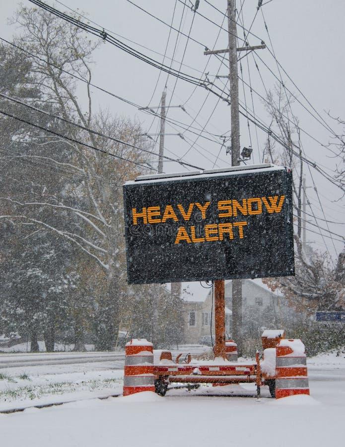 由一条积雪的路的边的电公路交通流动标志有暴雪戒备的雪下跌的警告的 图库摄影