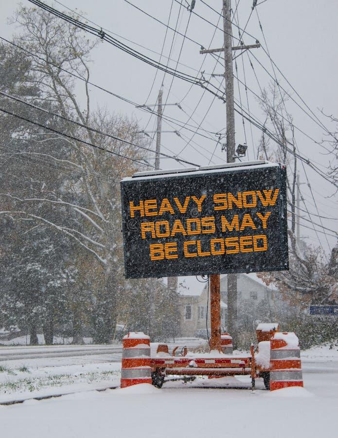 由一条积雪的路的边的电公路交通流动标志有暴雪戒备的雪下跌的警告的 免版税图库摄影