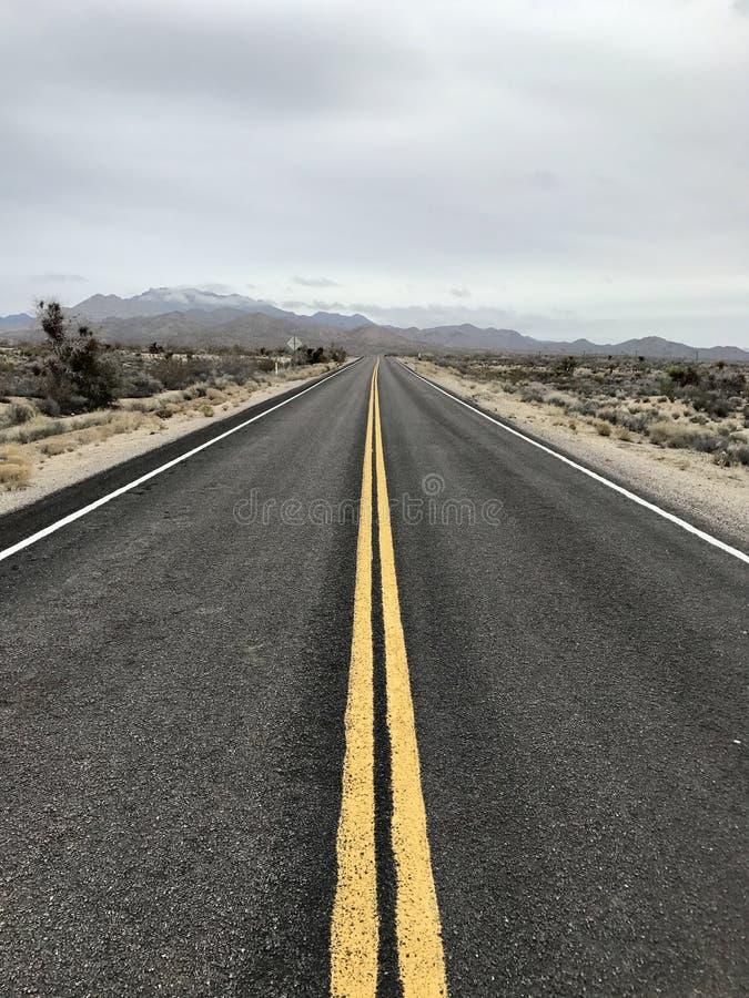 由一片沙漠的长的偏僻的路山的 免版税库存照片