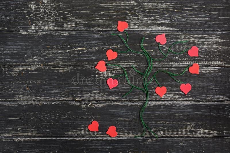 由与红色心脏的亚麻制螺纹做的一棵绿色树而不是叶子在木黑背景 日s华伦泰 图库摄影
