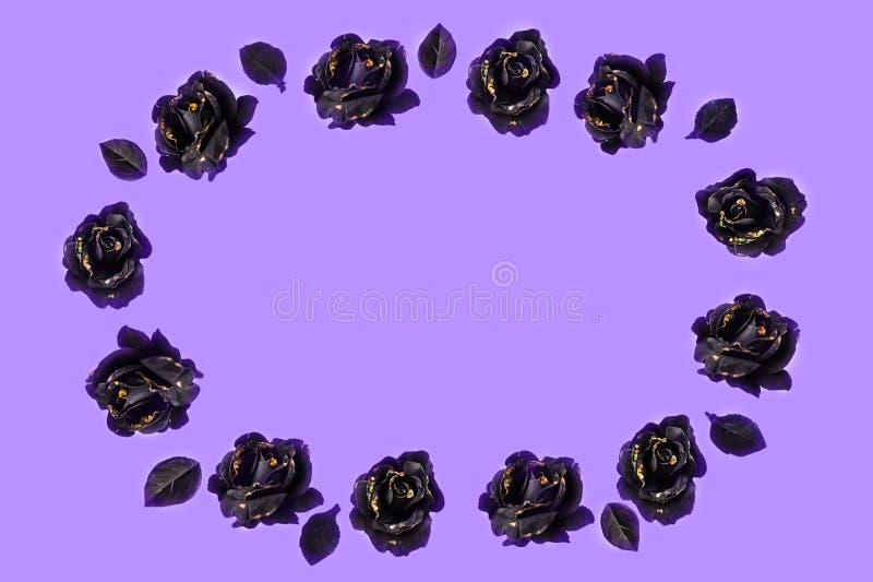 由与黑叶子的黑玫瑰做的祝贺的装饰品在淡紫色背景 库存图片