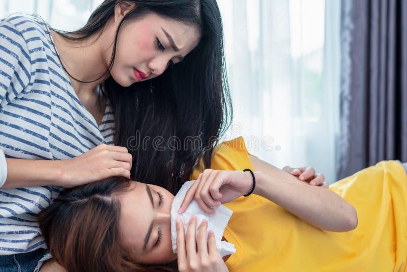 由于从男朋友的伤心亚洲姐妹安慰秀丽哀伤的女孩 人们和社会问题问题概念 图库摄影