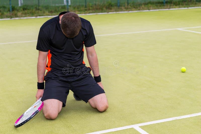 由于在tenni的损失年轻男性球员在他的膝盖跌倒了 免版税库存照片