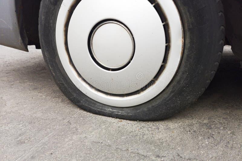 由于钉子打碎的车胎泄漏 在路的平的轮胎 Flatten刺了自动轮子 一辆汽车的损坏的泄了气的轮胎在路的 库存照片