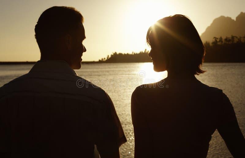 由享受日落的湖的夫妇 免版税图库摄影
