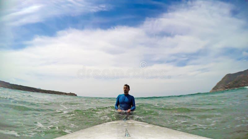 由他的冲浪板的冲浪者在水 库存照片