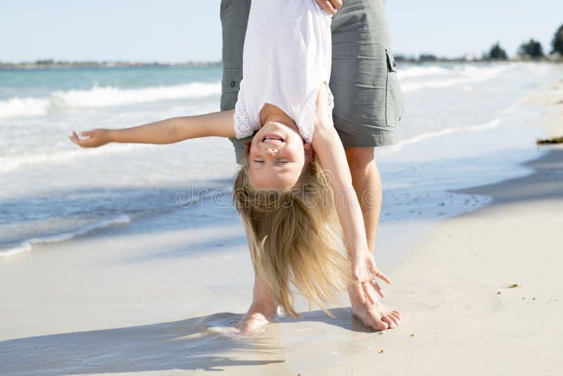 由使用她的脚生拿着甜年轻和可爱的白肤金发的小女儿获得在海滩的乐趣在爸爸和小女孩爱 免版税库存照片