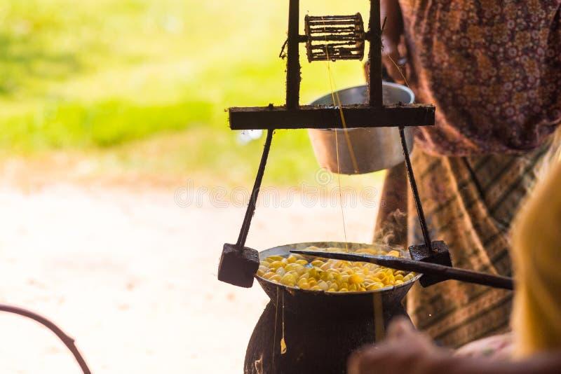 由做丝绸螺纹的锅炉的煮沸的黄色桑蚕茧 库存照片