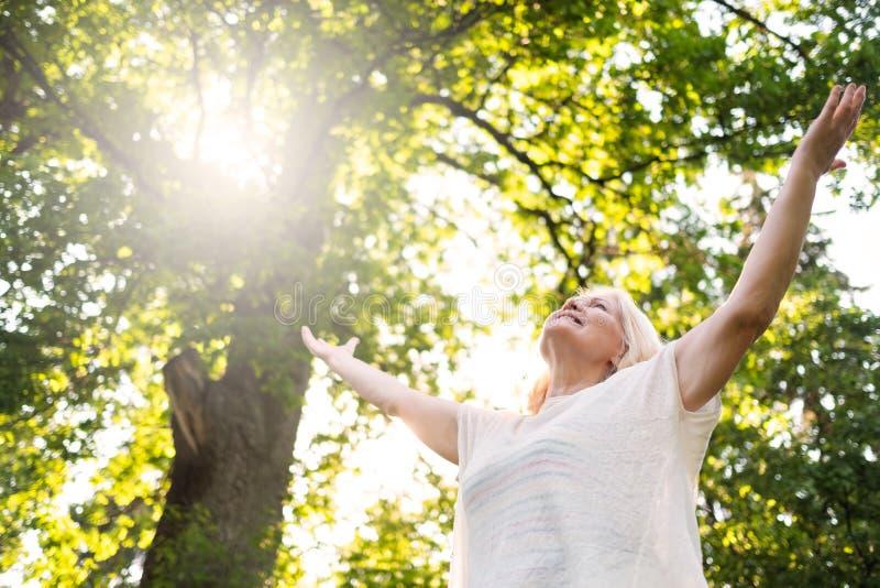 由停滞手的树的资深斯堪的纳维亚妇女 免版税库存照片