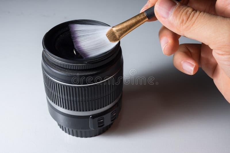 由刷子的清洁透镜 库存照片