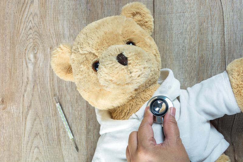 由医生的不适的玩具熊心脏听诊器有温度计的 免版税图库摄影