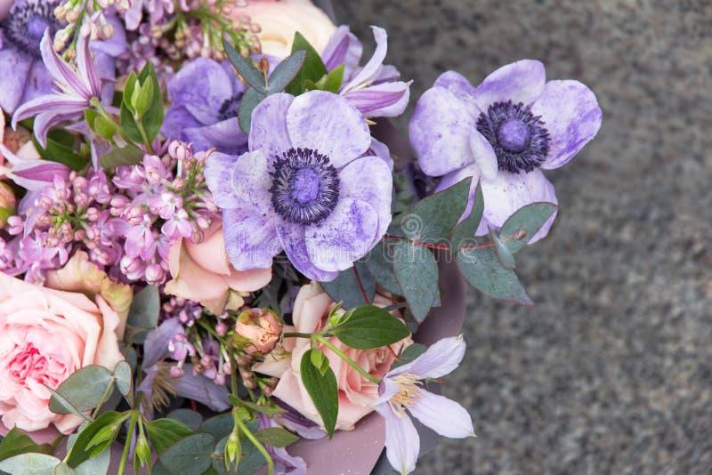 花卉,花背景 由卖花人的美丽的紫罗兰色花束有另外花和玫瑰特写镜头的 免版税库存图片