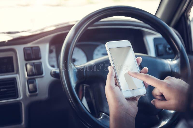 由叫发短信和看在一台手机的机动性的亚洲妇女谈话,当坐在她的汽车,酒后驾车,时 免版税库存照片