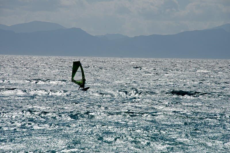 由后照与风帆冲浪的人的剪影的海景 免版税库存照片