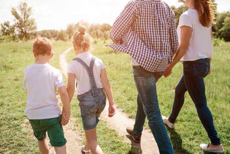由后面被做的图片 愉快的家庭通过草甸一起走 男孩握他的手 库存照片