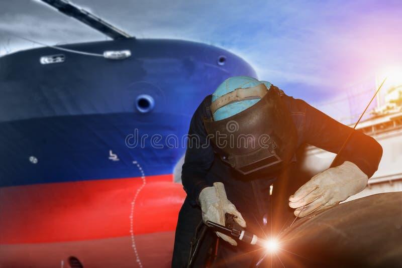 由向前船背景的产业工人焊接的船修理在造船厂 免版税库存图片