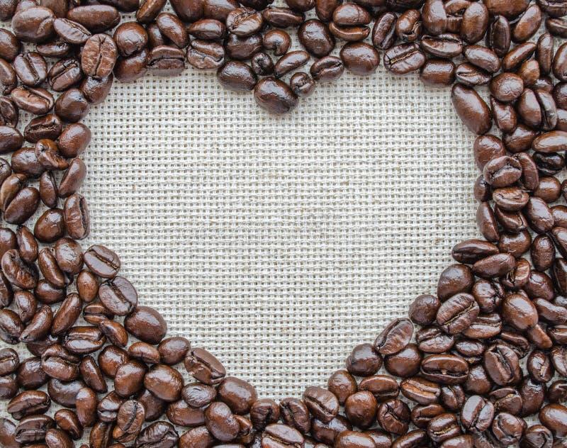 由咖啡豆做的心脏在织地不很细大袋 免版税库存照片
