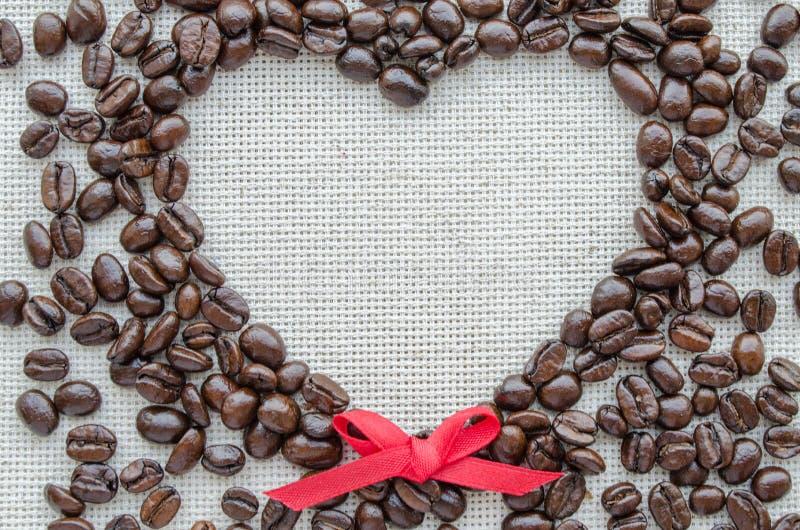 由咖啡豆做的心脏在织地不很细大袋 免版税库存图片