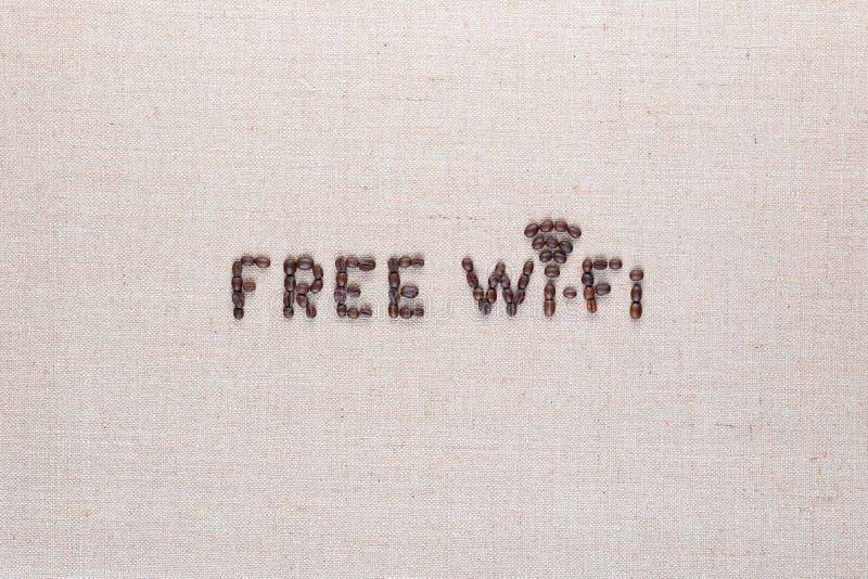 由咖啡豆做的自由wifi标志在linea背景,顶视图,被排列的中心 免版税库存图片