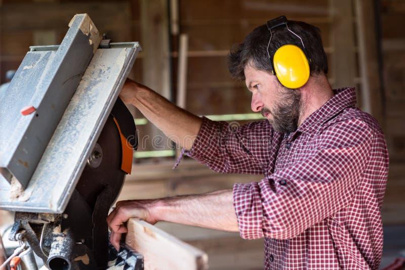 由圆锯的男性木匠切口板条 免版税库存图片