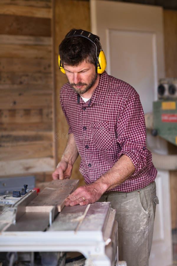 由圆锯的男性木匠切口板条 库存图片