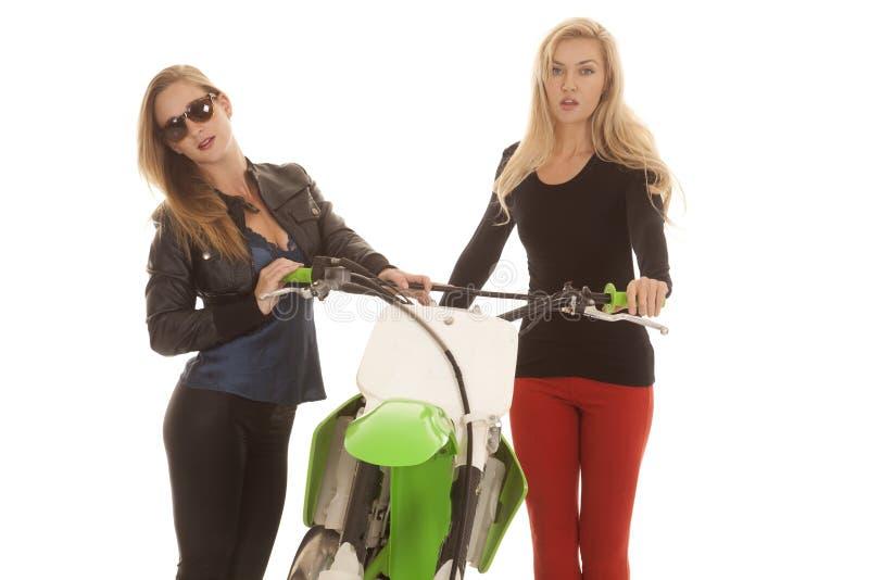 由土的两名妇女骑自行车一在玻璃 免版税库存照片
