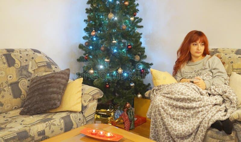 由圣诞树哀伤的调查的孤独的妇女距离 免版税库存照片