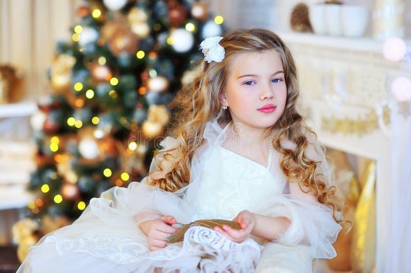 由圣诞树的可爱的女孩 库存图片