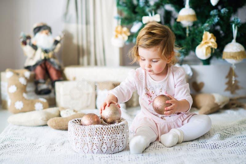 由圣诞树的可爱的小女孩 免版税图库摄影