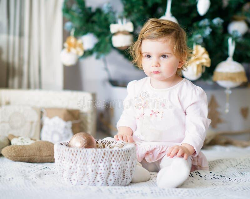 由圣诞树的可爱的小女孩 免版税库存照片