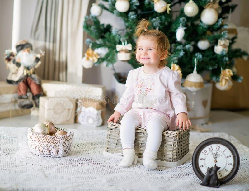 由圣诞树的可爱的小女孩 免版税库存图片